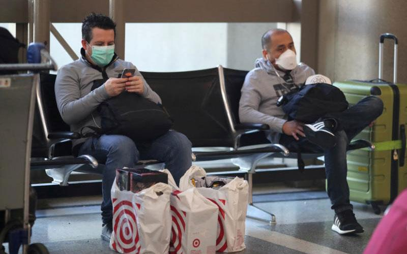 Passengers are seen wearing protective masks at LAX airport in Los Angeles March 11, 2020, during the coronavirus outbreak.