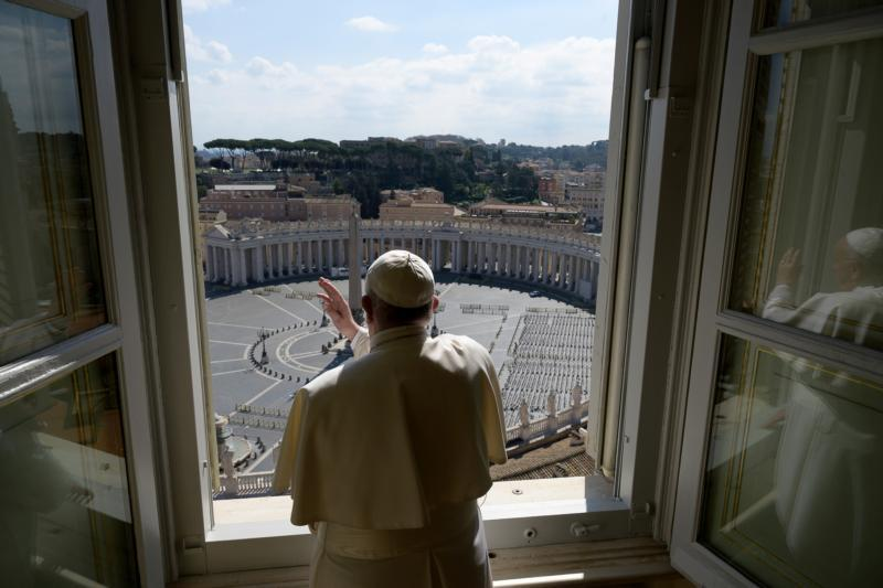 Standing in the window of the library of the Apostolic Palace overlooking an empty St. Peter's Square, Pope Francis blesses the city of Rome March 15, 2020, still under lockdown to prevent the spread of the coronavirus