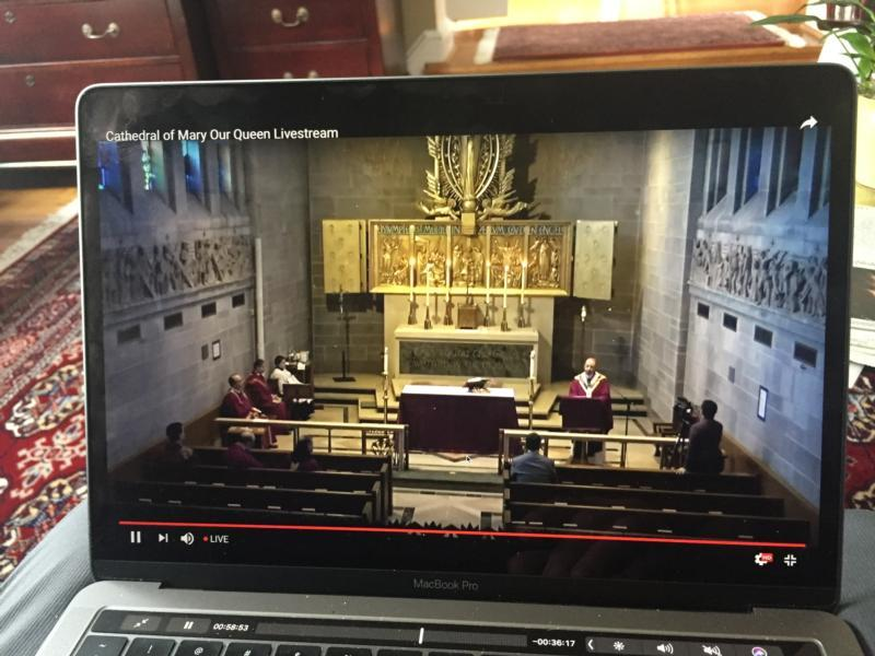 A viewer watches a livestream Mass from the Cathedral of Mary Our Queen in Baltimore celebrated by Baltimore Archbishop William E. Lori and a few concelebrants March 15, 2020.