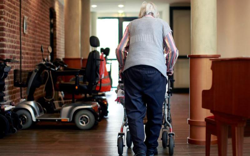 An elderly woman in Grevenbroich, Germany, walks through a corridor of a retirement home March 16, 2020.