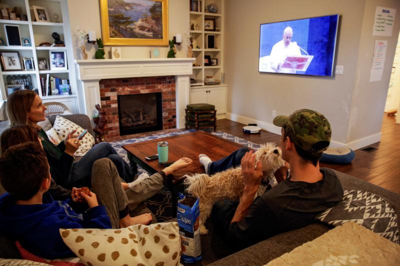 """The McClenahan family of Seattle watch Pope Francis' special prayer from the Vatican during the """"stay home, stay healthy"""" initiative March 27, 2020."""