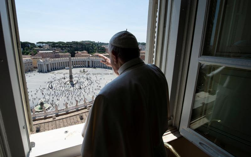 """Pope Francis waves as he looks out on St. Peter's Square after leading the """"Regina Coeli"""" from his library in the Apostolic Palace at the Vatican May 24, 2020."""