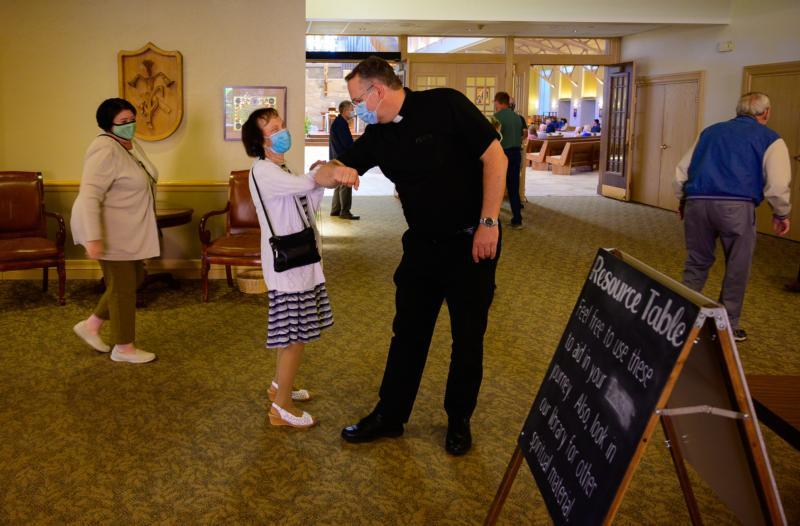 Father Peter Ambting, pastor of Our Lady of Lourdes Parish in De Pere, Wis., greets a parishioner before Mass June 14, 2020.