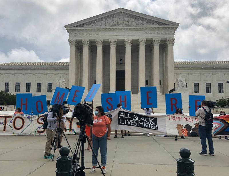 News crews film supporters of the Deferred Action for Childhood Arrivals program holding signs and cheering at the U.S. Supreme Court in Washington June 18, 2020, after the justices handed down a 5-4 ruling rejecting President Donald Trump's executive order to cancel DACA.