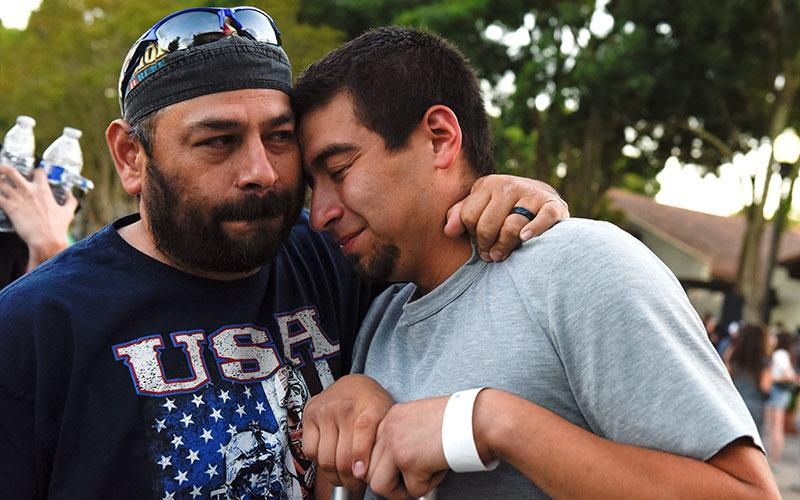 Justin Bates, right, a survivor of the Gilroy Garlic Festival mass shooting, is comforted by his father, Rob Bates, during a candlelight vigil outside Gilroy City Hall in California July 29, 2019.