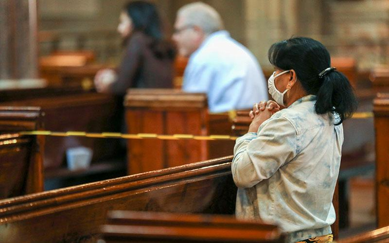A woman wearing a protective mask prays during Mass at the Catholic Church of the Immaculate Conception in London July 4, 2020, during the COVID-19 pandemic.