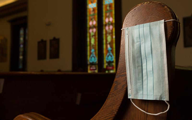 In this illustration photo, a disposable medical mask hangs on the side of a pew at Our Lady of Lourdes Church in Minneapolis.