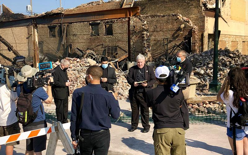 Archbishop Jerome E. Listecki of Milwaukee prays Aug. 27, 2020, at one of the Kenosha, Wis., sites destroyed during protests. Jacob Blake, a Black man, was shot seven times in the back Aug. 24 while entering his car with his three small children inside the vehicle.