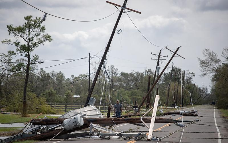 A man in Sulphur, La., walks past fallen electrical lines to get to his residence in the aftermath of Hurricane Laura Aug. 27, 2020.