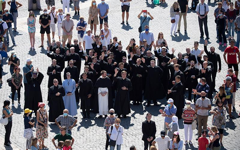 People wave as Pope Francis leads the Angelus from the window of his studio overlooking St. Peter's Square at the Vatican Sept. 6, 2020.