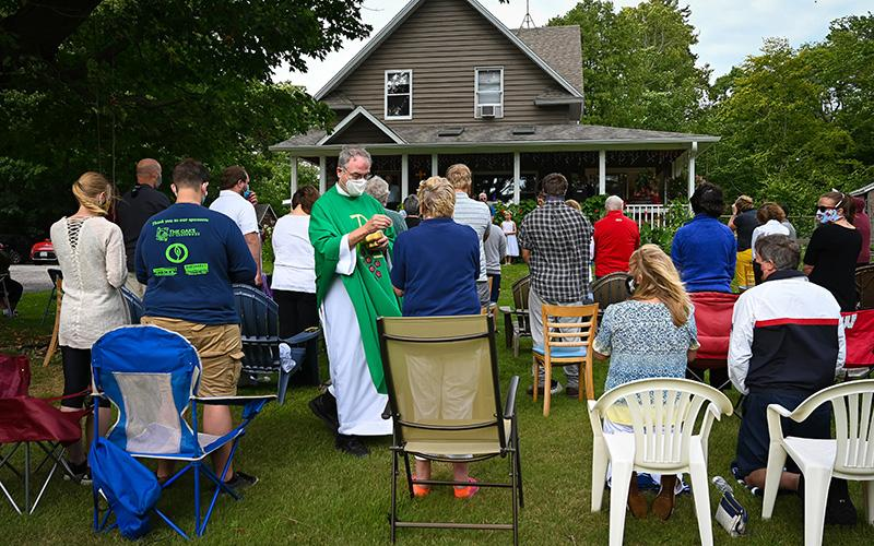 Father Tom Farrell, pastor of Stella Marish Parish in Door County, Wis., distributes Communion to people attending an outdoor Mass Sept. 6, 2020, at the home of Larry and Diane Kahlscheuer on Washington Island.