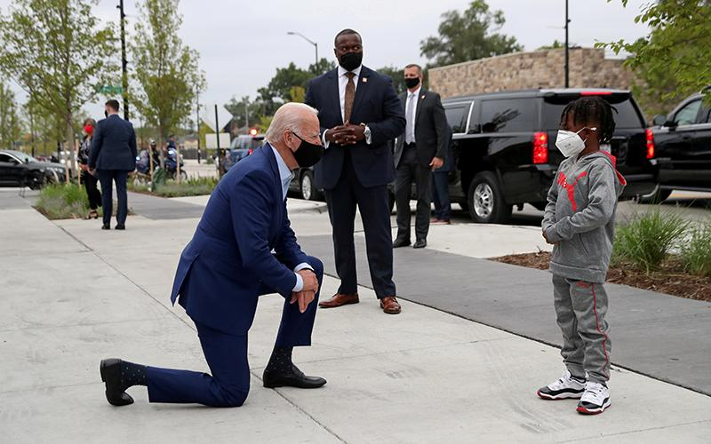 Democratic presidential nominee Joe Biden speaks to CJ Brown as he makes a brief stop at the Three Thirteen clothing store in Detroit to buy a few items for his grandchildren Sept. 9, 2020.