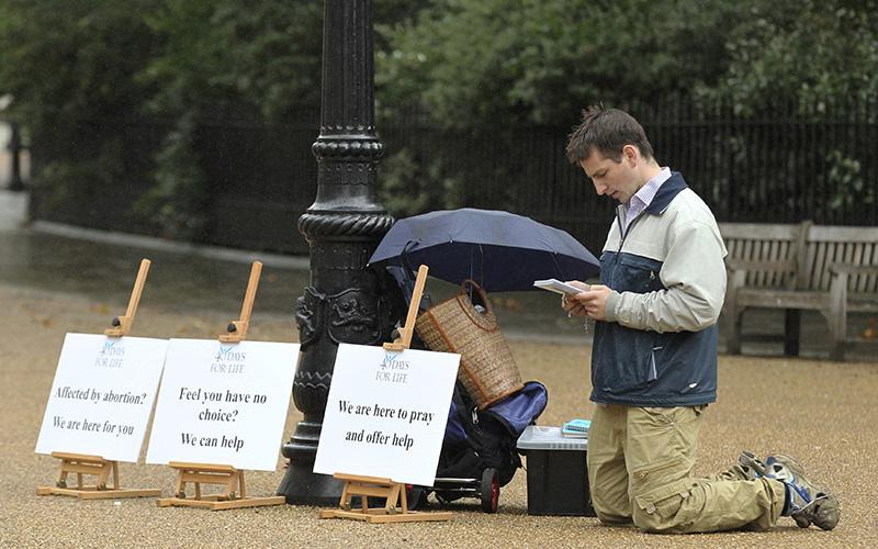 A pro-life activist is pictured in a file photo kneeling in prayer outside a London abortion clinic. British bishops have expressed sadness over an increase in abortion numbers.