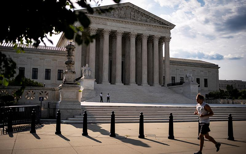 A man runs past the U.S. Supreme Court building in Washington June 25, 2020.