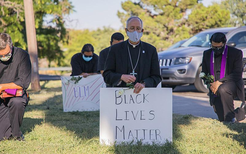 "Bishop Mark J. Seitz of El Paso, Texas, kneels at El Paso's Memorial Park holding a ""Black Lives Matter"" sign June 1, 2020."