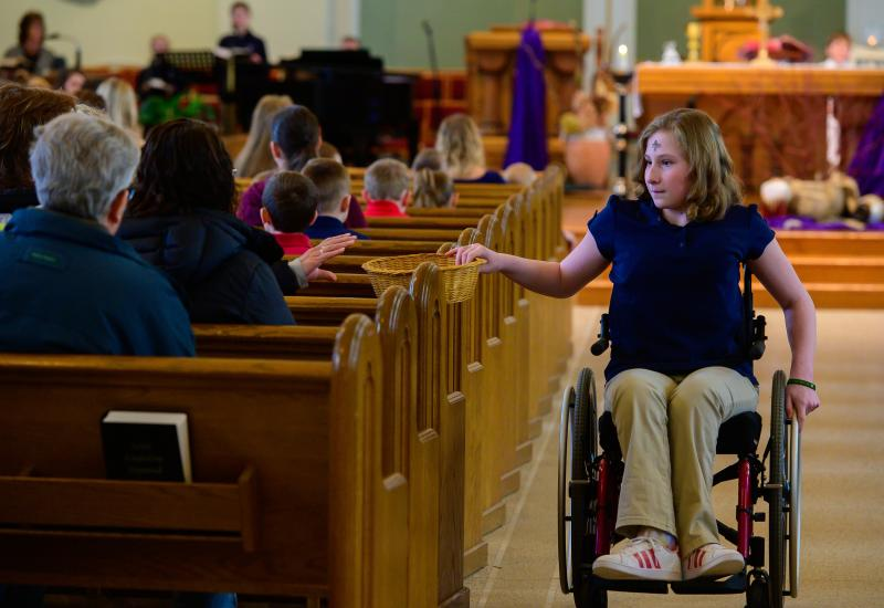Katelyn Vandenhandel, 13, a student at St. Nicholas School in Freedom, Wis., passes a collection basket during Ash Wednesday Mass at St. Nicholas Church Feb. 26, 2020.