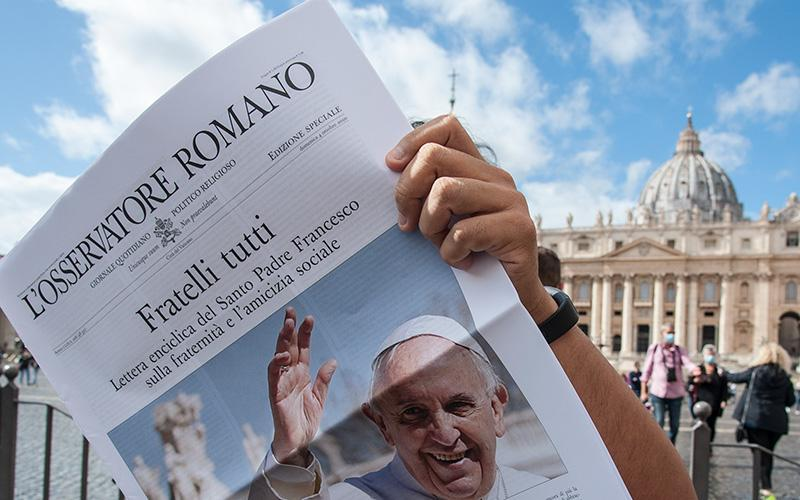 """Free copies of L'Osservatore Romano, the Vatican newspaper, with the front page about Pope Francis' new encyclical, """"Fratelli Tutti, on Fraternity and Social Friendship,"""" are distributed by volunteers at the end of the Angelus in St. Peter's Square at the Vatican Oct. 4, 2020."""