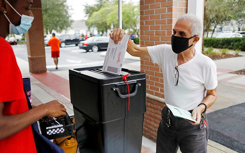 A man in Orlando, Fla., casts his mail-in ballot Oct. 19, 2020, as early voting begins ahead of the November election.