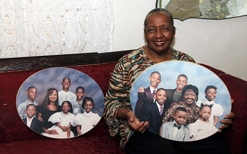 Sharonell Fulton, a member of St. Barbara Parish in Philadelphia, displays pictures of some of her foster children in this 2015 file photo.