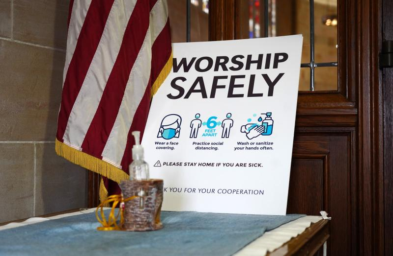 Health guidelines on preventing the spread of COVID-19 and a hand-sanitizer dispenser are seen near an entrance to Immaculate Conception Church in Jamaica Estates, N.Y., Nov. 22, 2020.