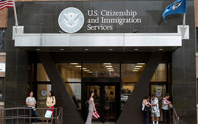 People stand on the steps of the U.S. Citizenship and Immigration Services offices in New York City Aug. 15, 2012.