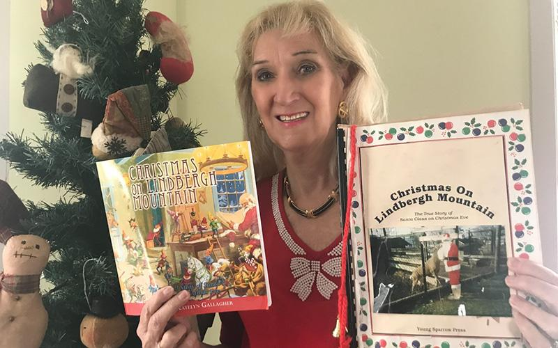 "Patricia Mohan Gallagher, pictured in her home in Worcester, Pa., Nov. 20, 2020, holds up two copies of the book she co-wrote with her daughter Katelyn, ""Christmas on Lindbergh Mountain: The True Story of Santa Claus on Christmas Eve."""