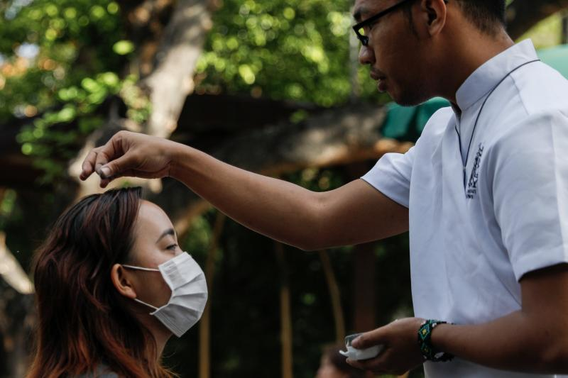 A woman wearing a protective mask receives ashes on top of her head during Ash Wednesday Mass at the National Shrine of Our Mother of Perpetual Help in Manila, Philippines, Feb. 26, 2020, during the COVID-19 pandemic.