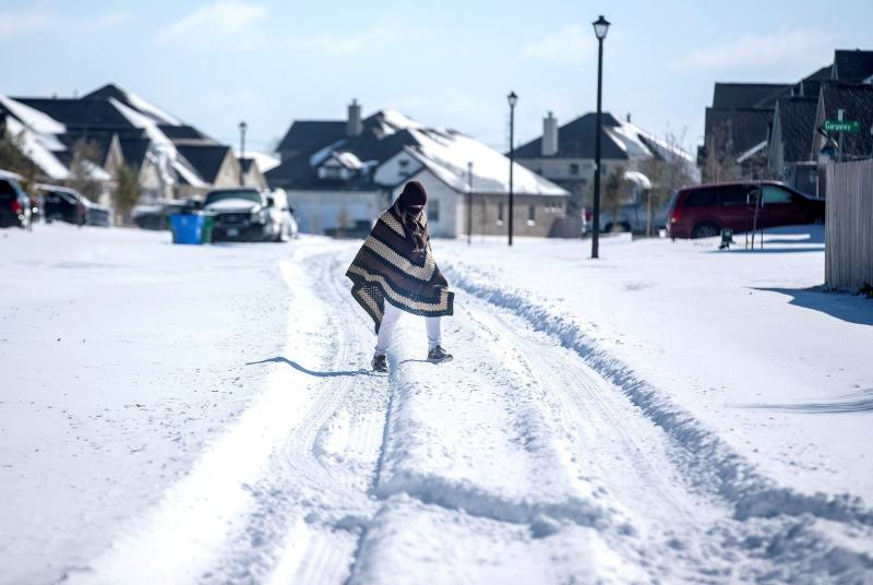 A man in Pflugerville, Texas, walks to his friend's house Feb. 15, 2021, in a neighborhood that had no electricity.