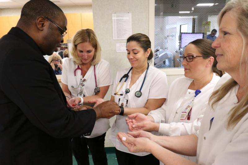 Father Corneille Boyeye, chaplain at St. Catherine of Siena Medical Center in Smithtown, N.Y., and a member of the Missionaries of the Sacred Heart, anoints the hands of Cecilia Prado, center, and other nurses in the hospital's telemetry unit May 7, 2018.