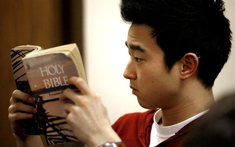A young man looks up a Scripture passage during Bible study.