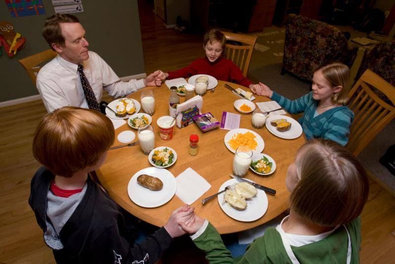 A family prays before eating a meatless meal of baked potatoes and salad at their home.