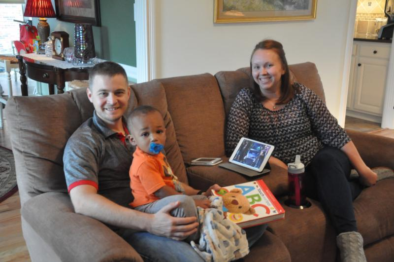Jaxson Amschler, then 18 months old, sits with his father, Joe Amschler, and his mother, Jenni Amschler, at their home in Kentucky.