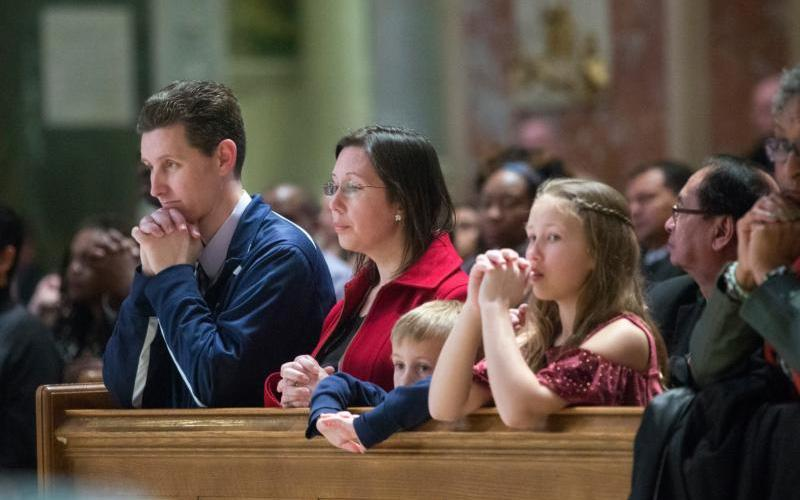 A family prays during Mass at the Cathedral of St. Matthew the Apostle in Washington. Parenthood unfolds over decades, traversing a course that is alternately joyful and confounding, replete with moments to celebrate or lament.