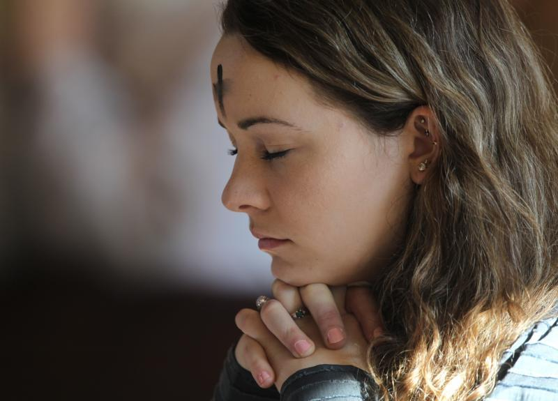 A young woman prays during Ash Wednesday Mass at Jesus the Divine Word Church in Huntingtown, Md., March 6, 2019.