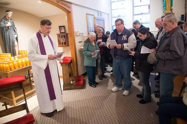 <p>Father Frank Lioi leads a prayer service at the shrine of St. Peregrine at St. Francis of Assisi Church in Auburn March 6.  </p>