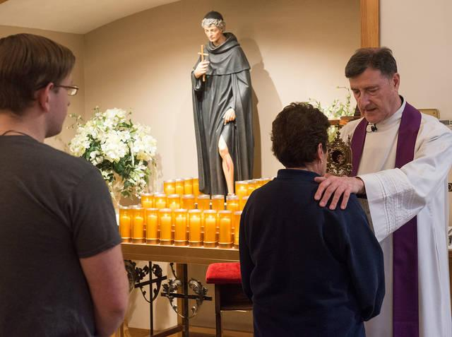<p>Father Frank Lioi blesses people with a relic of St. Peregrine during a prayer service at St. Francis of Assisi Church in Auburn March 6.  </p>