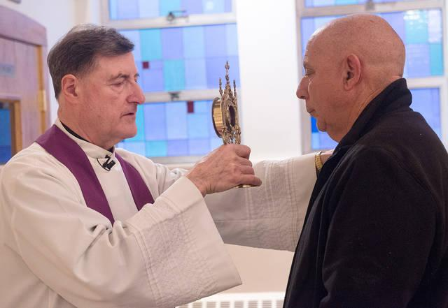 <p>Father Frank Lioi blesses Bob Bruno with a relic of St. Peregrine during a prayer service at St. Francis of Assisi Church in Auburn March 6.  </p>