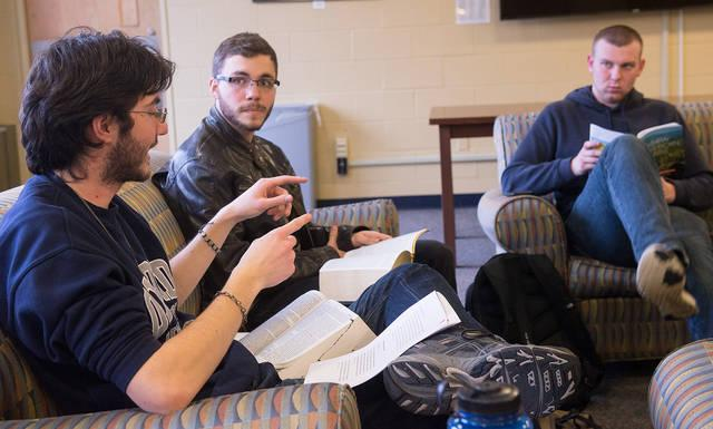 <p>University of Rochester students David Marshall (center) and Tucker McKeown (right) listen to FOCUS missionary Jim Davey as he leads a Bible-study group on campus March 27.  </p>