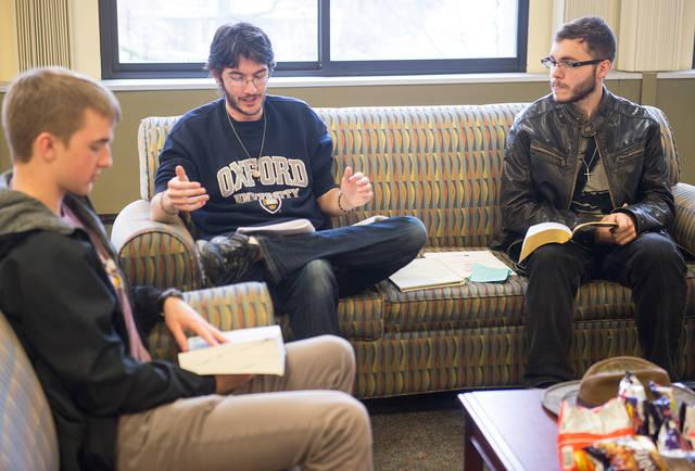 <p>University of Rochester students Dane Johnson (left) and David Marshall (right) listen to FOCUS missionary Jim Davey as he leads a Bible-study group on campus March 27.  </p>