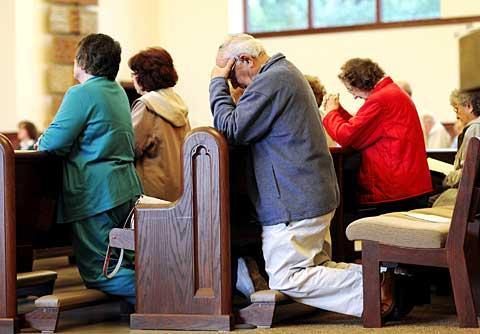 Parishioners pray during a Sept. 27, 2009, Mass at Our Lady of Mercy Church in Greece. The June 27 final Mass and June 30 closing date for the church were recently set.