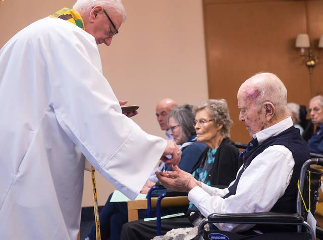 """<p>Father Ed Palumbos presents John """"Jack"""" Reinhardt with an award April 3 for his service at Fairport Baptist Homes' weekly Mass. Reinhardt, 95, has served as a lector in the past and currently is the usher and greeter for the liturgies. (Courier photo by John Haeger)  </p>"""