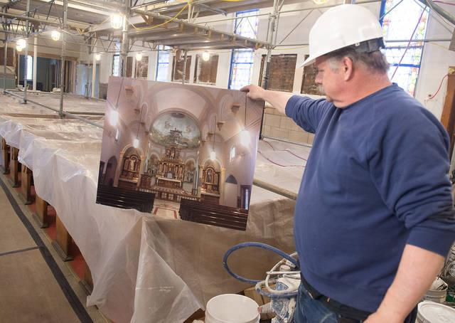 <p>Project manager Frank Marianacci holds up an artist&rsquo;s rendering April 11 of some of the renovation work being done at Our Lady of Victory Church in Rochester. It is the first major renovation to be undertaken at the church since a fire there in 1912. (Courier photo by John Haeger) </p>