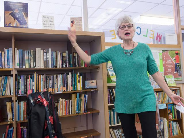 <p>Carolyn Simolo talks about the new library at St. Francis and St. Clare Parish's Ministry Center in Waterloo April 22.(Courier photo by John Haeger) </p>