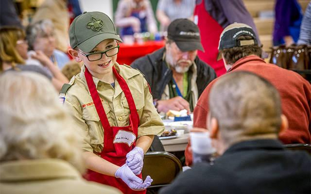 <p>Boy Scout Mathias Warner helps serve meals May 16 during the annual Free Spaghetti Supper sponsored by Elmira's Blessed Sacrament Parish. Blessed Sacrament, Christ the Redeemer and St. Mary Southside will transition into a single citywide parish effective July 1. (Photo by Rick Bacmanski) </p>