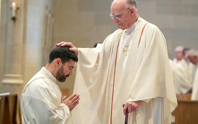 <p>Msgr. Gerard Krieg lays his hand on Father Jeff Chichester&rsquo;s head during Father Chichester&rsquo;s ordination June 2. (Courier photo by Jeff Witherow)  </p>