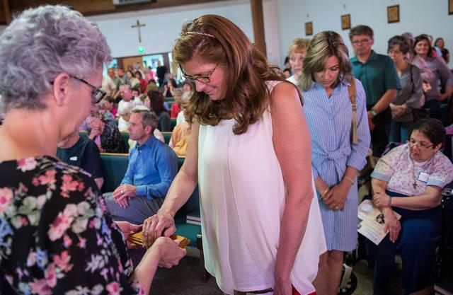 <p>During a Lourdes Virtual Pilgrimage Experience May 8 at Auburn&rsquo;s Sacred Heart Church, Sharon Nelson places her hand on a rock from the grotto where Mary reportedly appeared to St. Bernadette Soubirous.  </p>