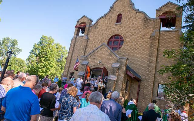 <p>Parishioners of St. Pius V Church in Cohocton gather outside for a cornerstone blessing by Bishop Salvatore R. Matano July 8 in celebration of the building&rsquo;s 100th anniversary. (Courier photo by Jeff Witherow)  </p>