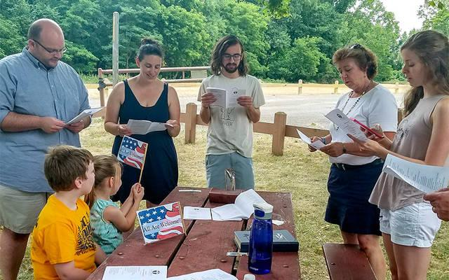 """<p>Members of Irondequoit's Saint Kateri Parish recite evening prayer at Camp Eastman July 13 as part of the newly introduced """"Pop-up Prayer Gardens."""" (Courier photo by Mike Latona) </p>"""