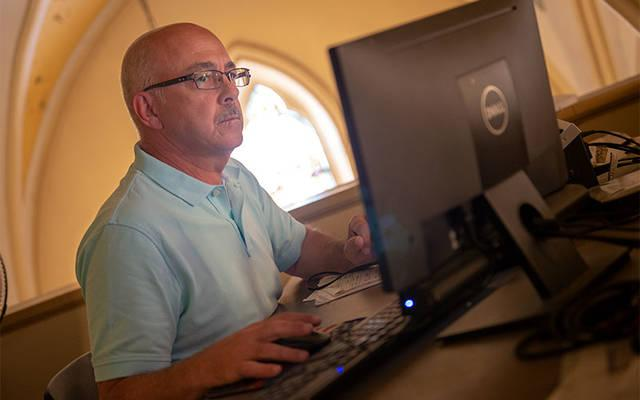 <p>Video operator Mike Paulin looks over the camera feed during a Sept. 15 Mass at Corning's St. Mary Church. (Courier photo by Jeff Witherow)  </p>