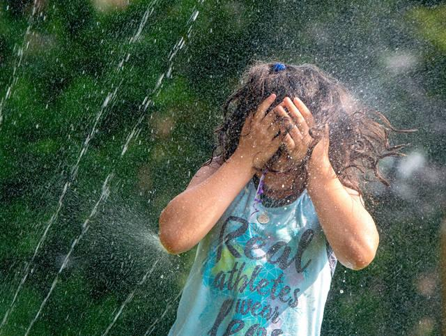 <p>Second-grader Maria Carbone cools off under the sprinkler during the Fun Fest at St. Joseph School in Penfield June 18.  </p>